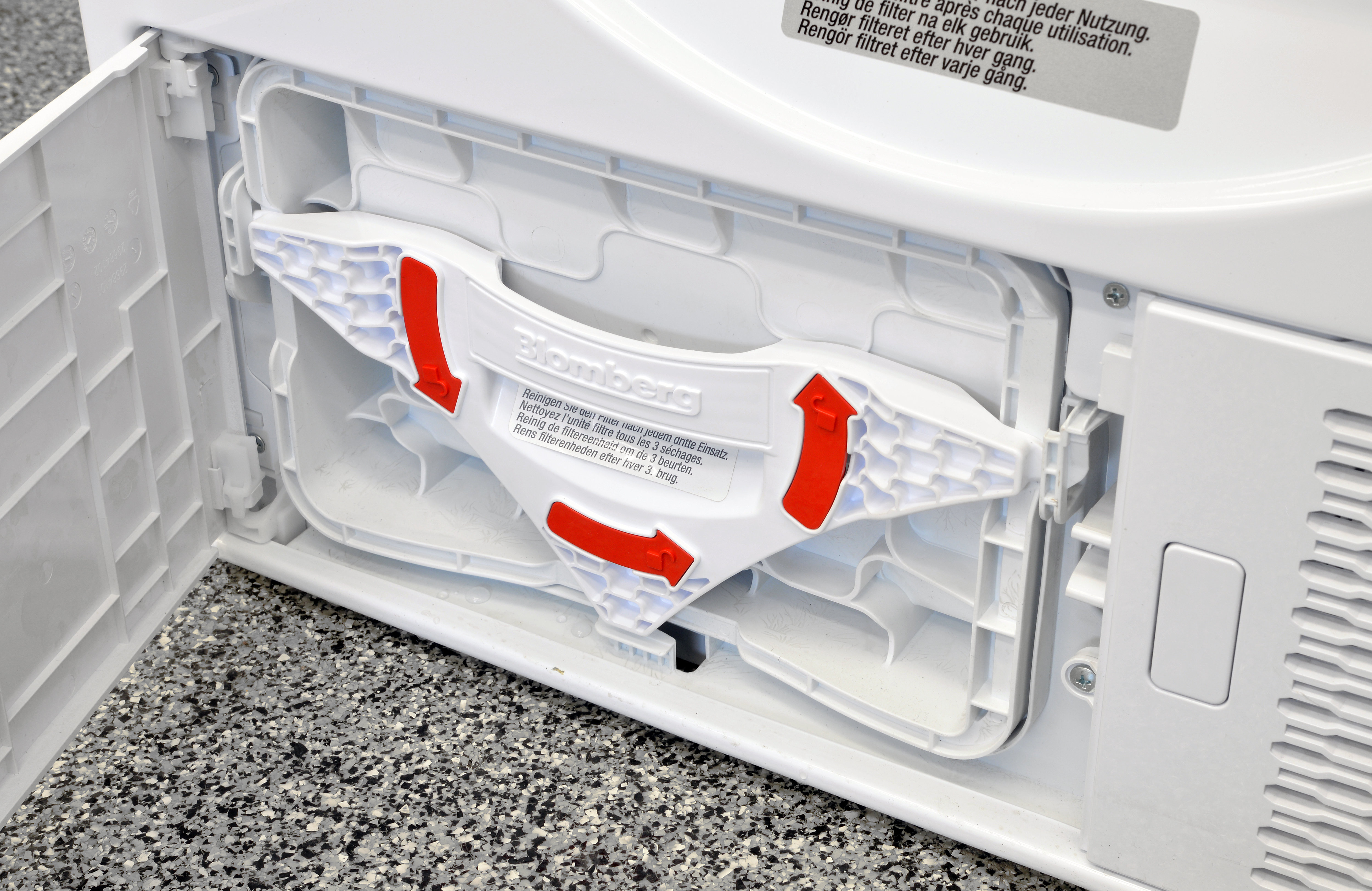 Bright red arrows remind users how to release the Blomberg DHP24412W's secondary lint trap.